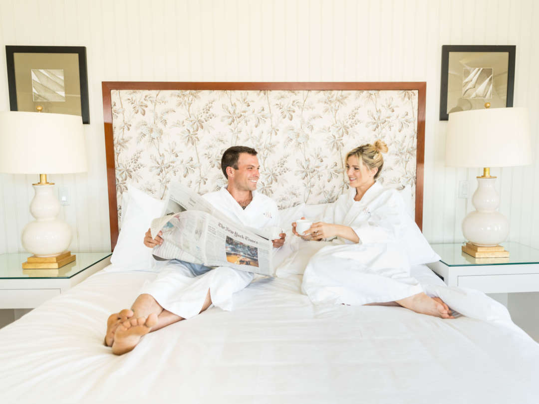 A couple in robes laying in bed in a newly renovated room reading the newspaper and relaxing