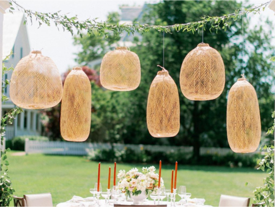 Straw lanterns hanging from a piece of garland over a wedding table
