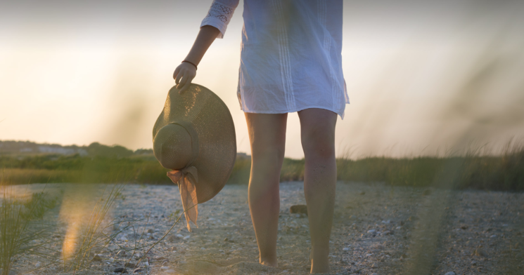 Woman walking on the beach holding her straw hat in her hand