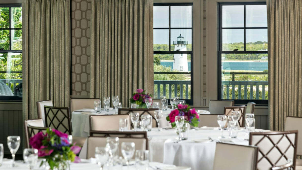 Dining room with view of the lighthouse and harbor set up with white table clothes and place settings and floral center pieces