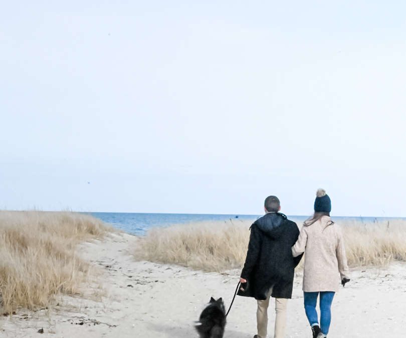 Couple walking their dog on the beach in the fall