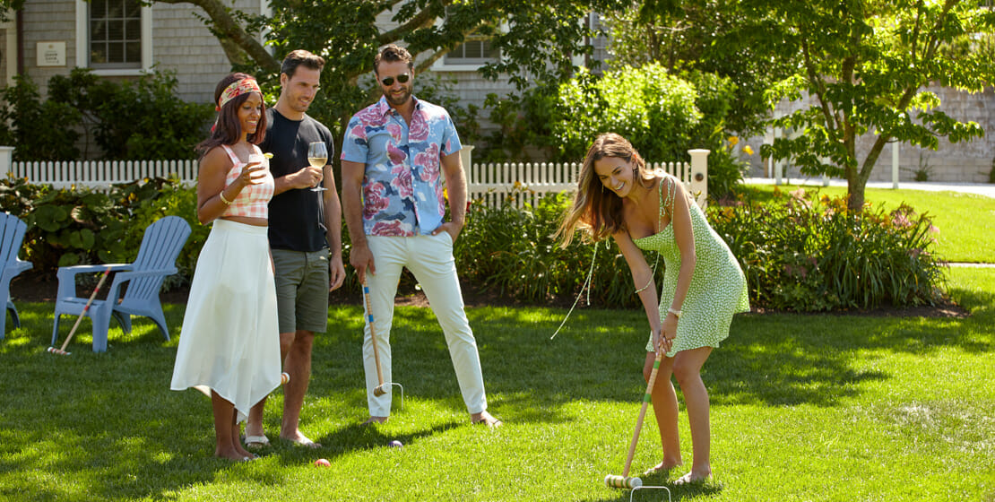 Two couples playing croquet