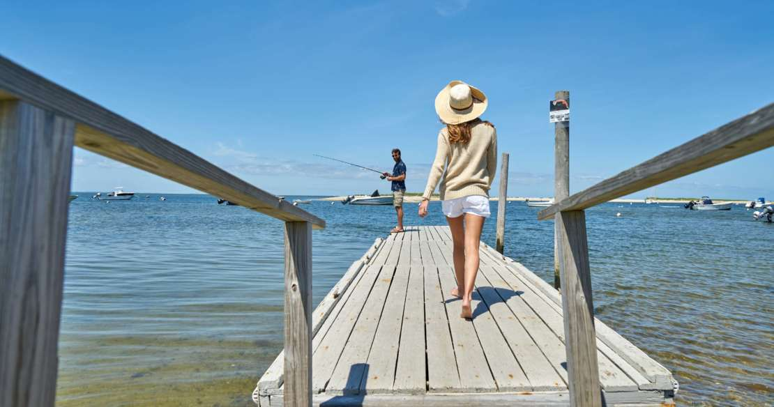 Woman walking on a dock toward her husband fishing