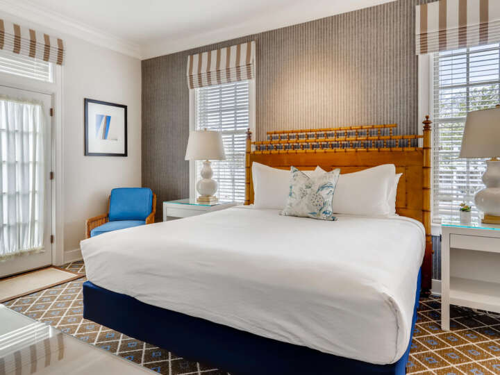 a king bed in a room with a blue chair