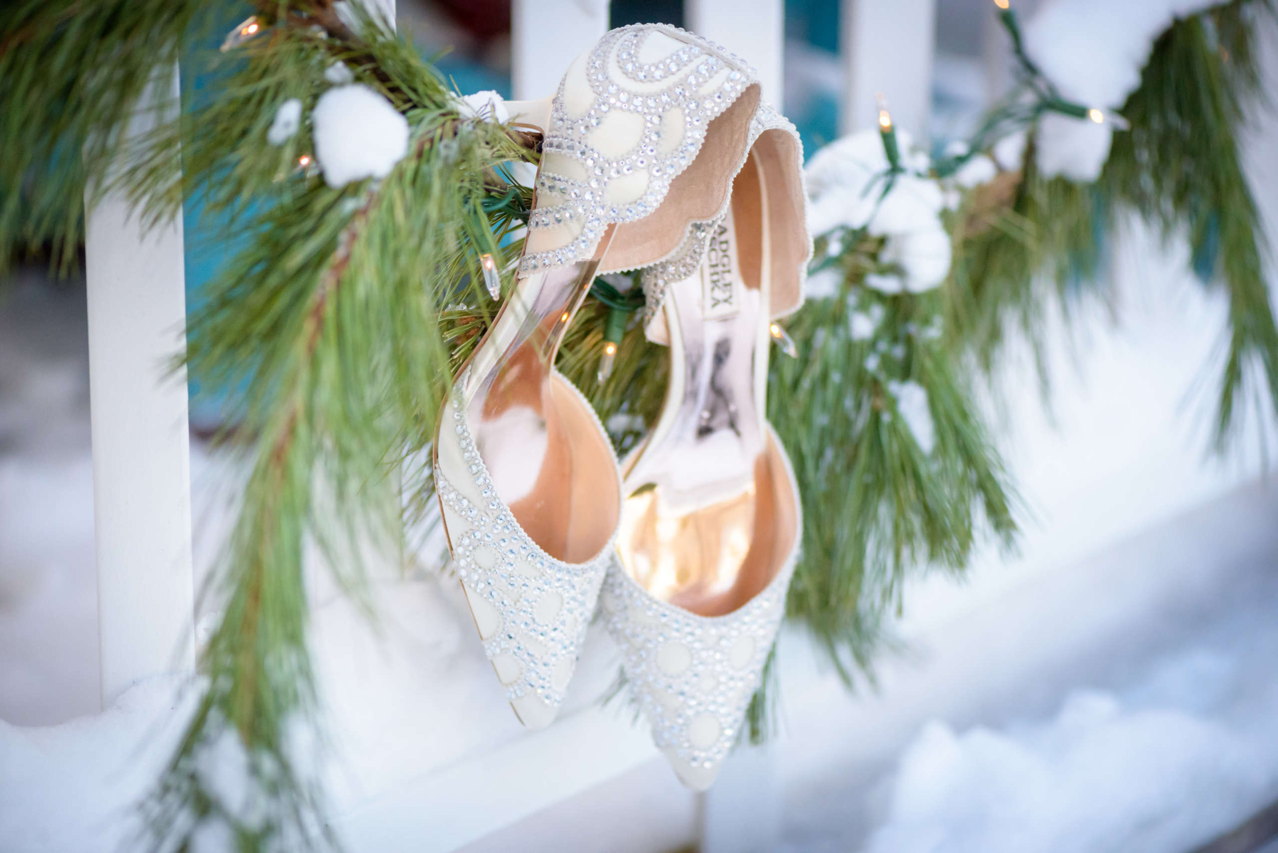 Close up photo of bride's wedding shoes hanging on garland in winter