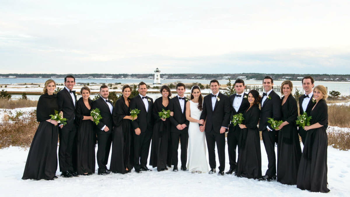 Bride and groom with wedding party taking photos outside in winter