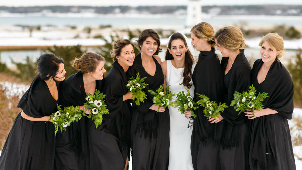 Bride and bridesmaids taking photos outside in winter
