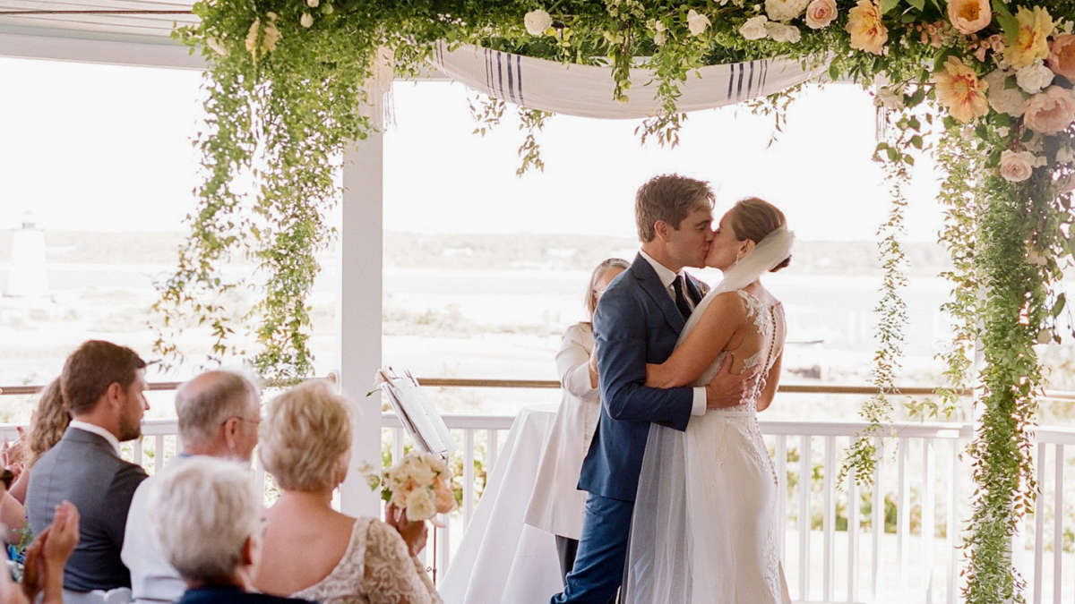 Bride and groom kissing at the alter