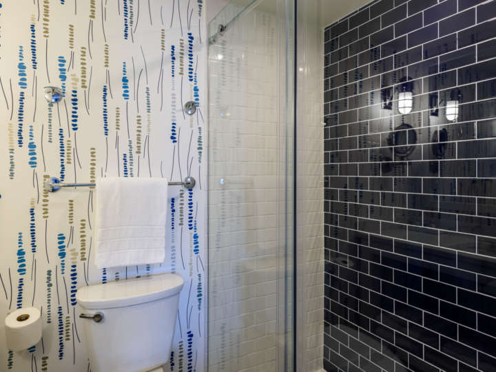 Renovated bathroom with blue tiles in the shower