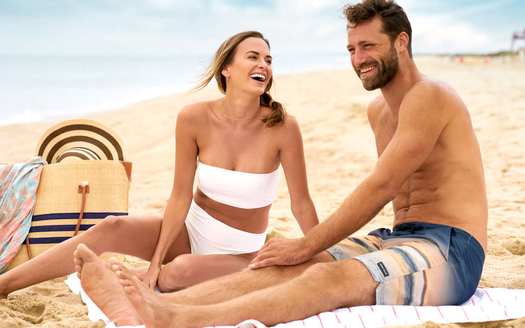 Couple sitting and laughing on the beach together