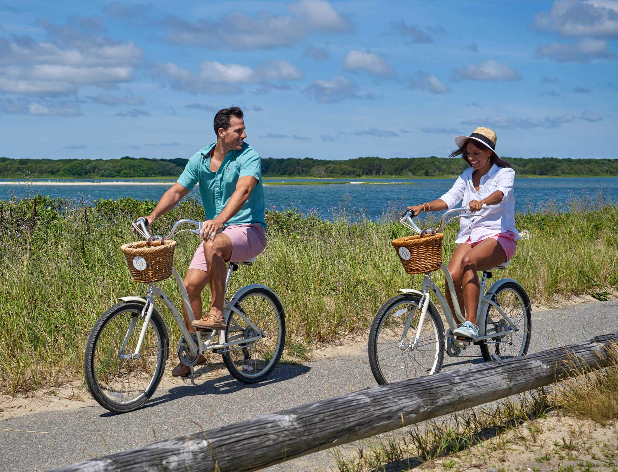 Couple riding bikes by the shore together