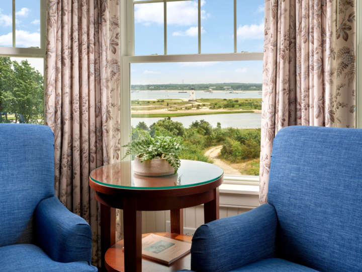 Two blue arm chairs by a window with beautiful views of the harbor