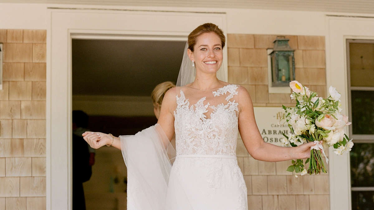 Bride holding up her train smiling on the deck