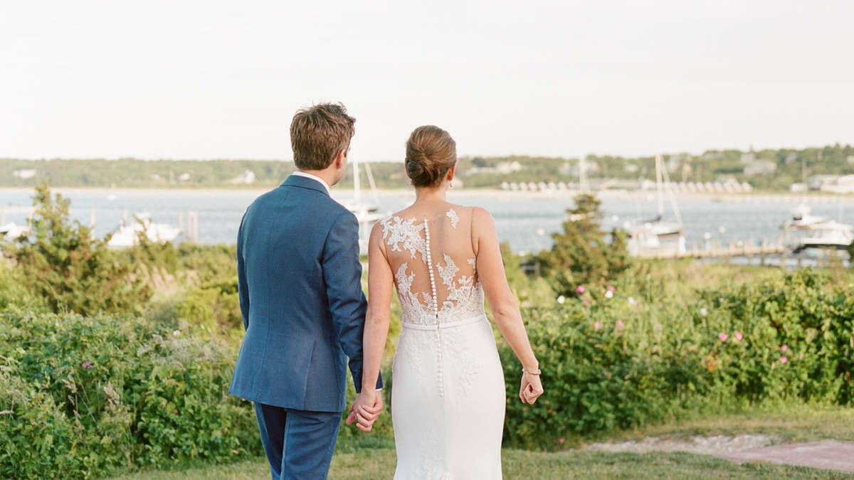 Bride and groom holding hands looking out at the view together