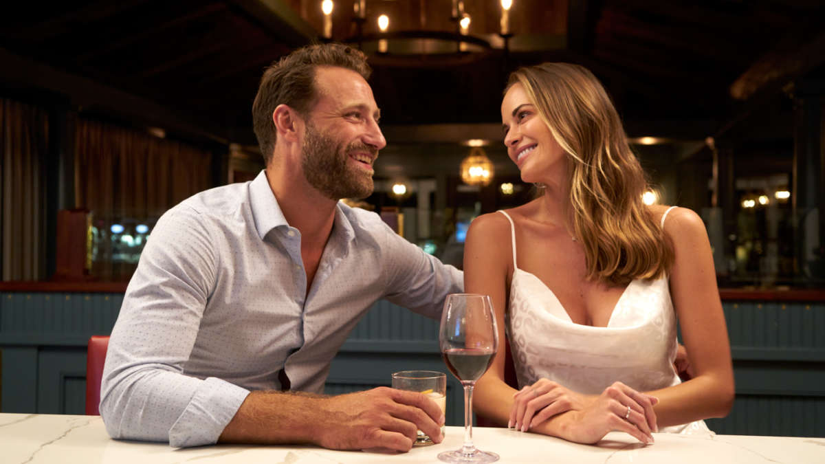 A couple sitting at the bar together smiling and drinking wine