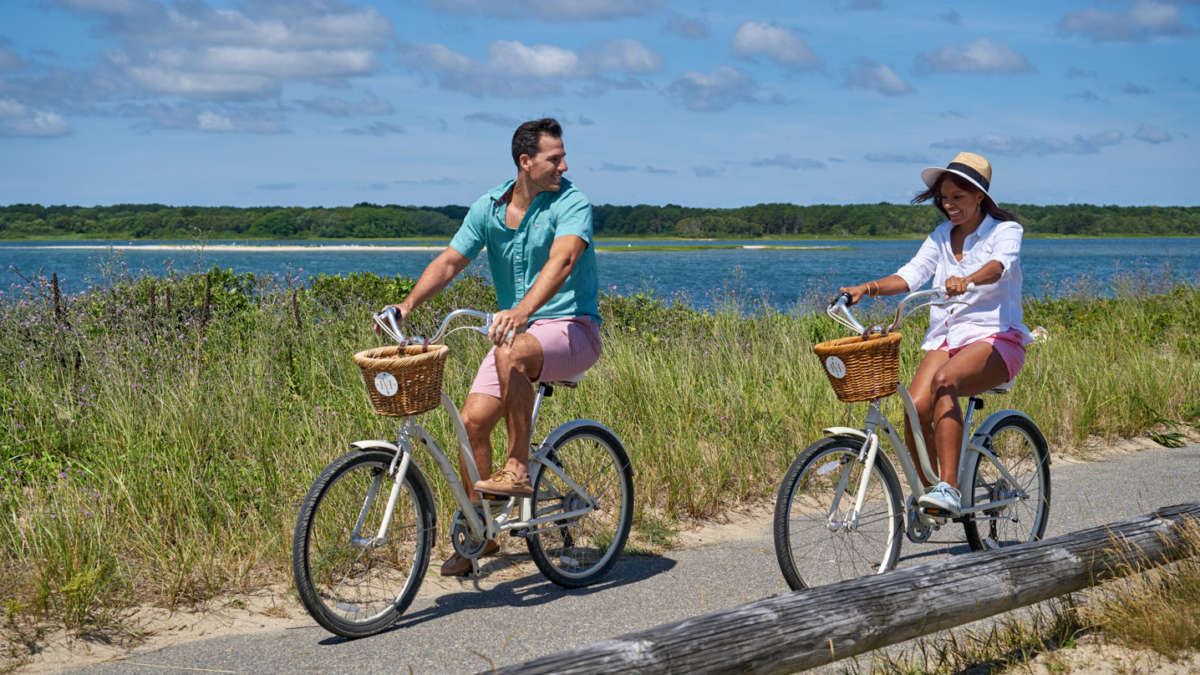 Couple riding bikes next to the shore