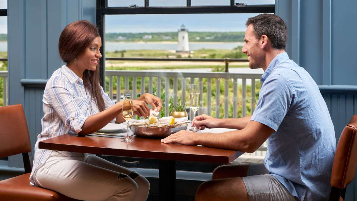 Couple eating dinner at a table with a view of the harbor