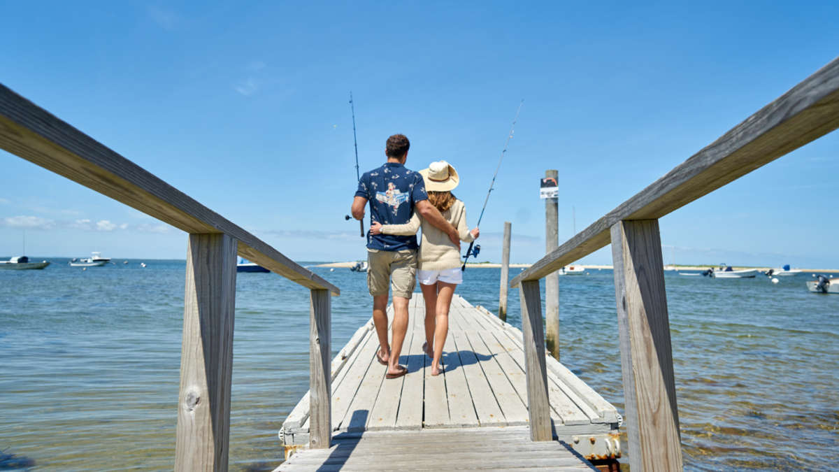 Couple walking arm in arm on a dock holding fishing poles