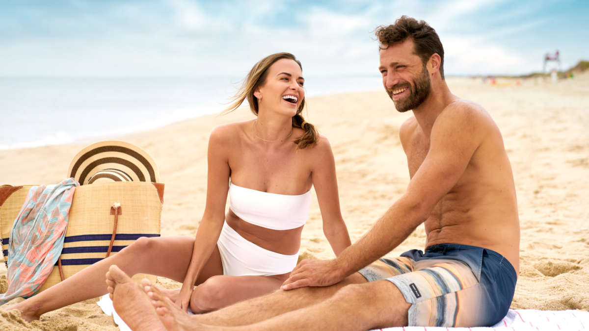Couple sitting on the beach laughing