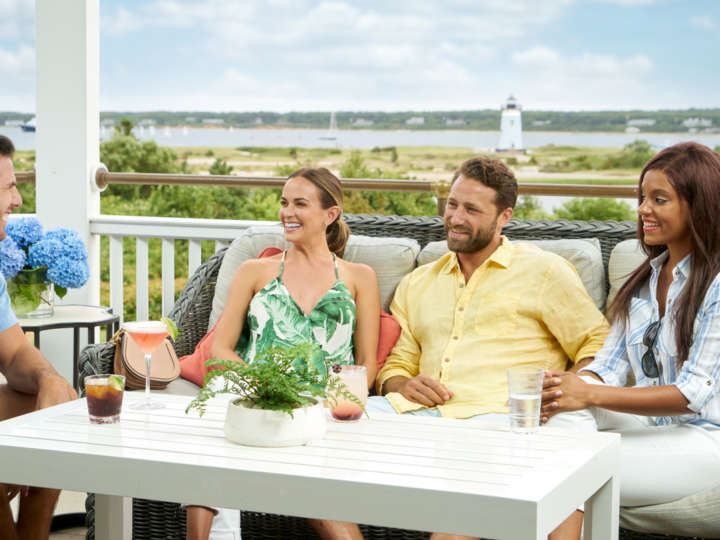 Two couples chatting and having drinks on the porch