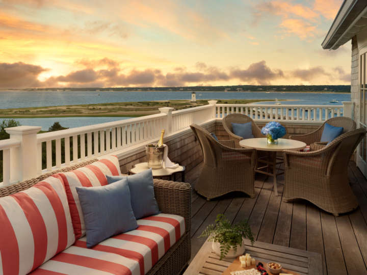 Deck with stunning sunset view and couch and table