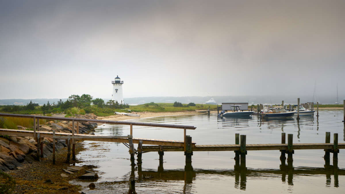 Dock on a calm foggy morning with the lighthouse in the background