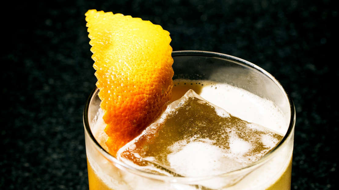 Drink with ice cube and wedge of lemon