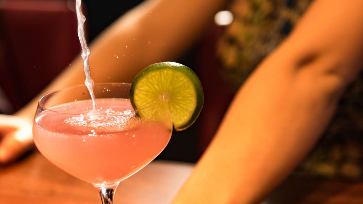 Pink drink with lime being poured
