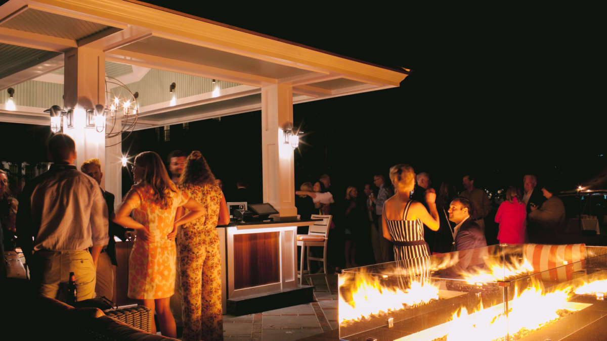 Guests chatting at the bar and around the fire pit at night