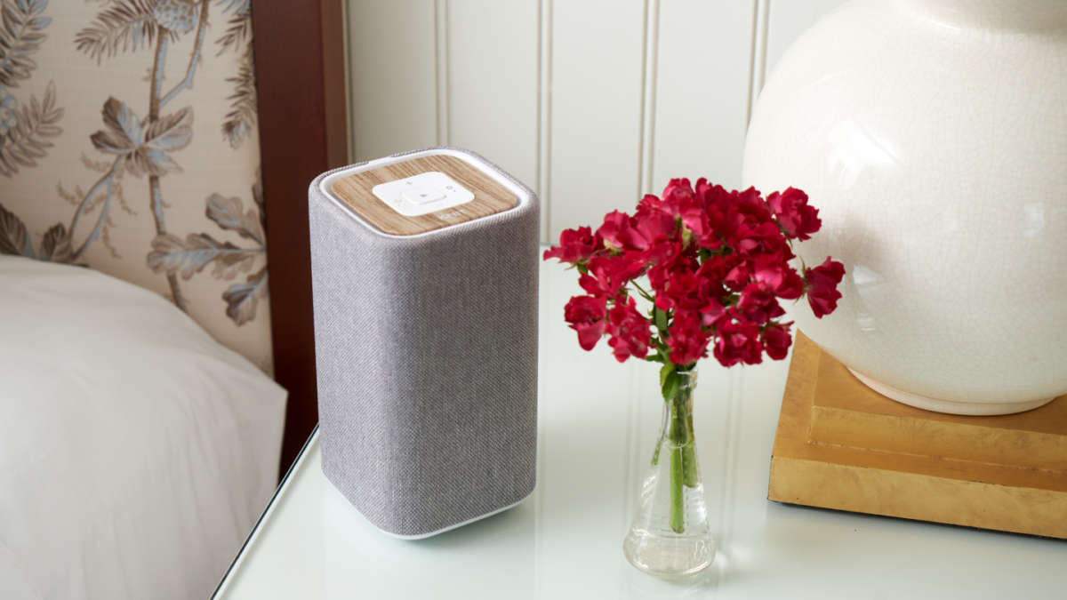 A speaker next to a vase of flowers on the bedside table