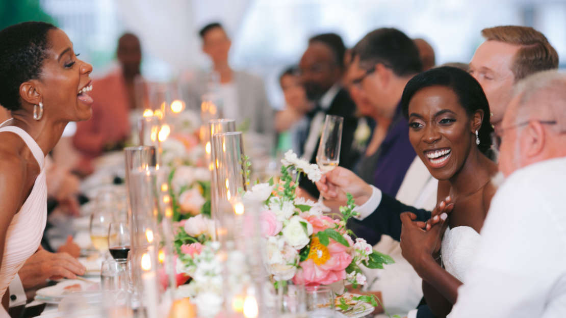 Bride and groom laughing at dinner table with guests