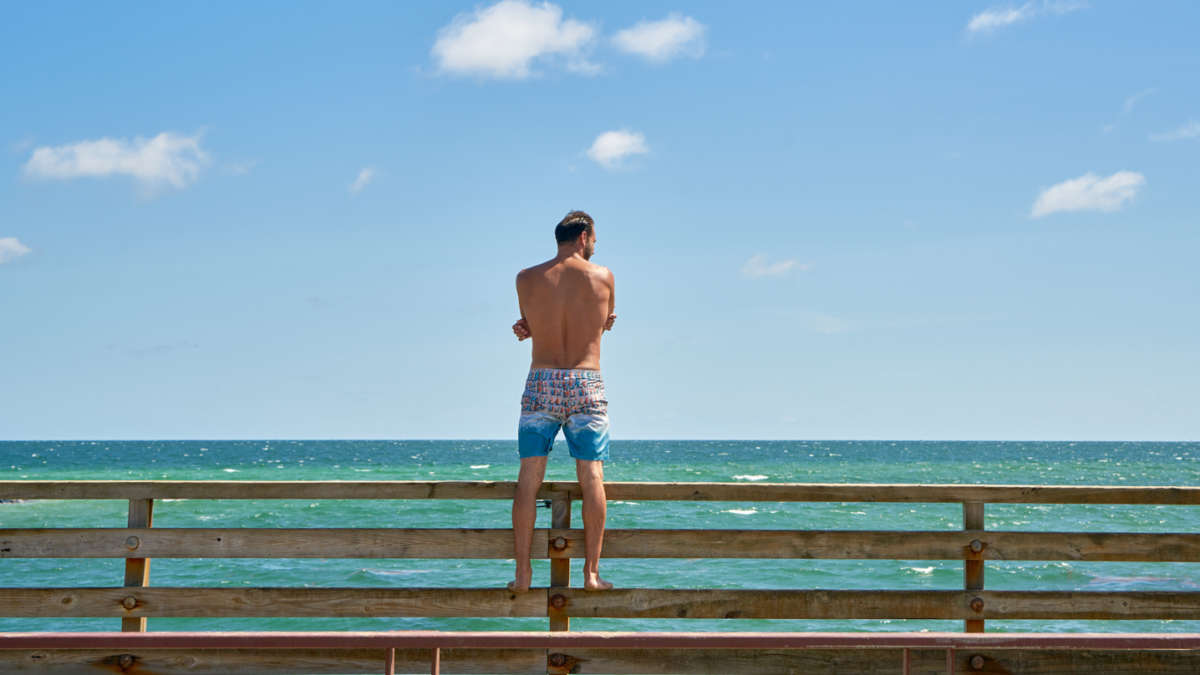 Man standing on the pier looking out toward the ocean
