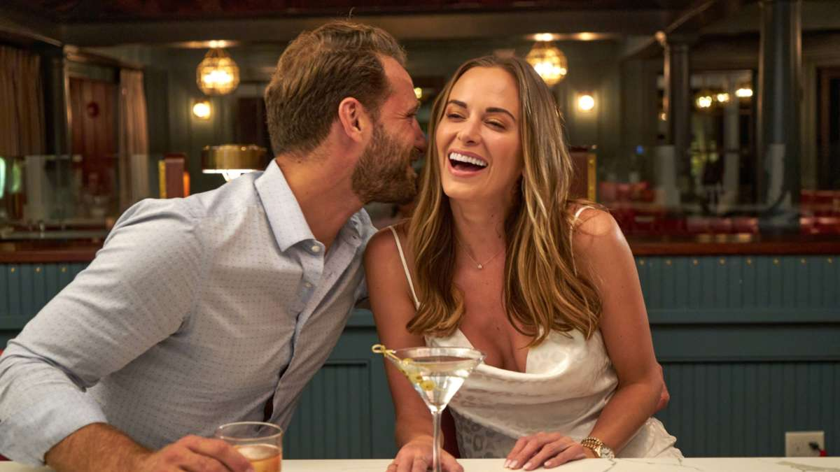 Man whispering into woman's ear at the bar
