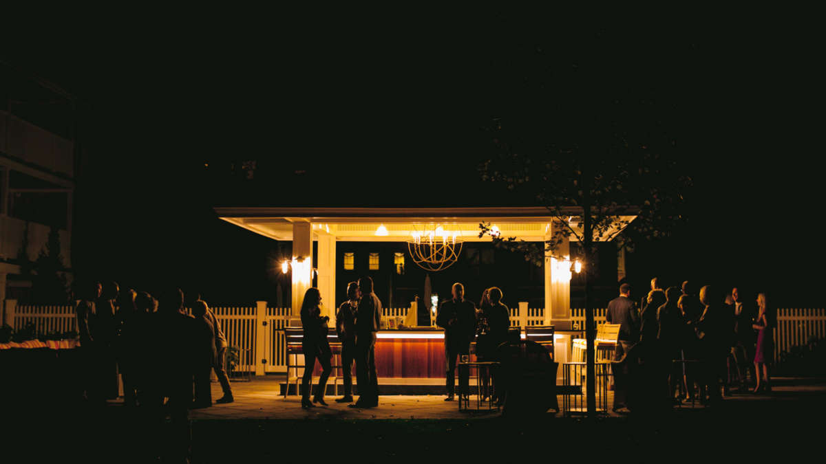 Guests mingling at night by the bar