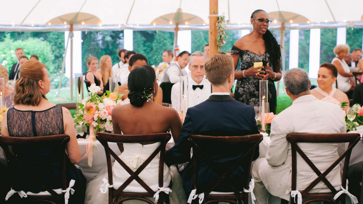 Bride and groom sitting at a table while family member gives a speech