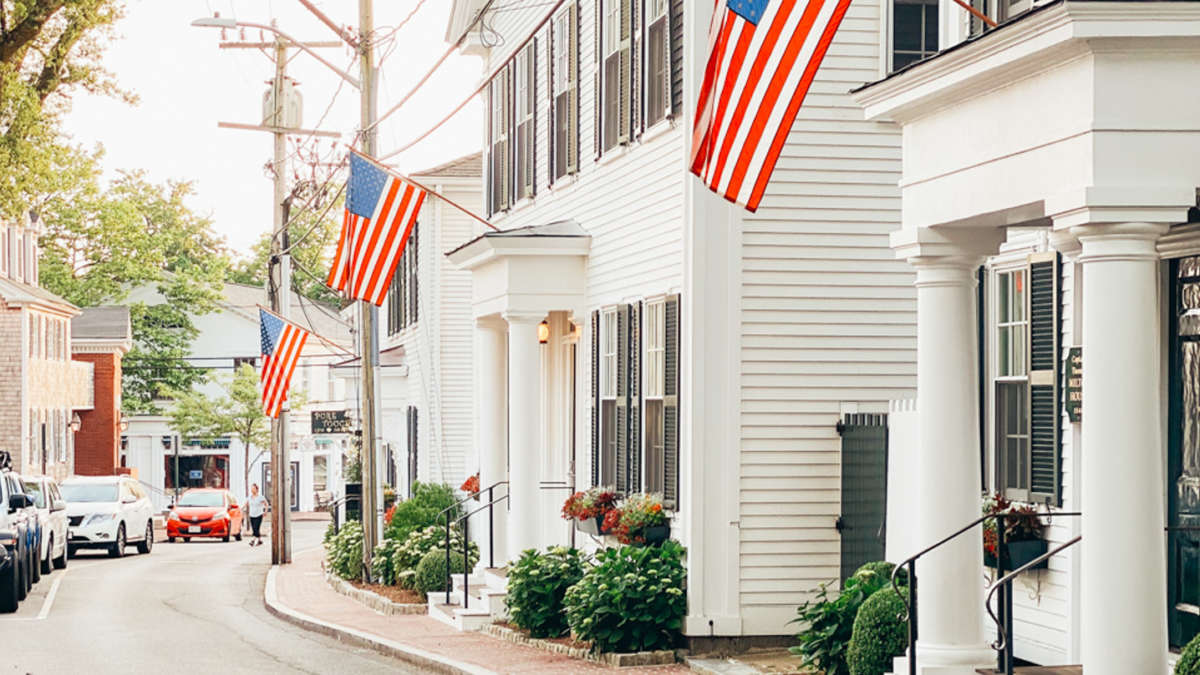 Street lined with white houses with American flags