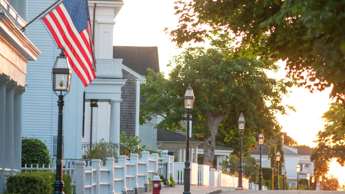 Street lined with white picket fences and American flags
