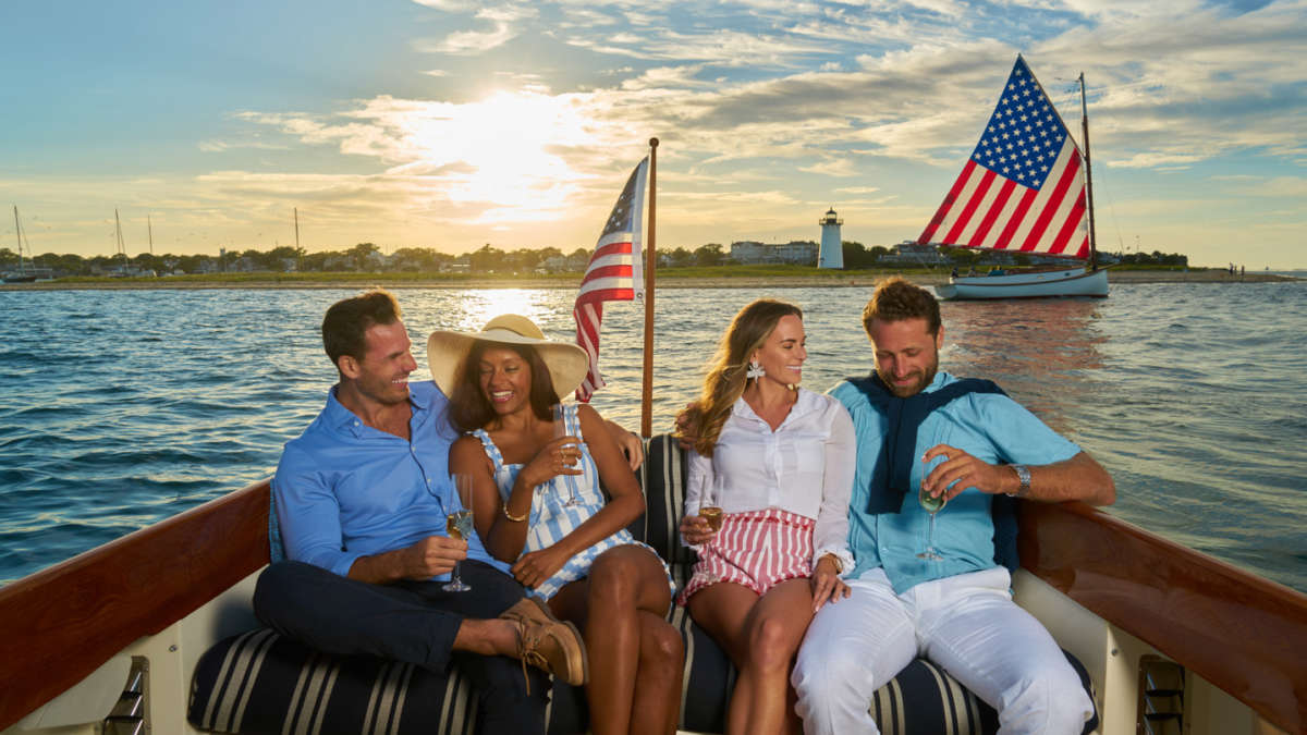 Two couples laughing on a boat at sunset