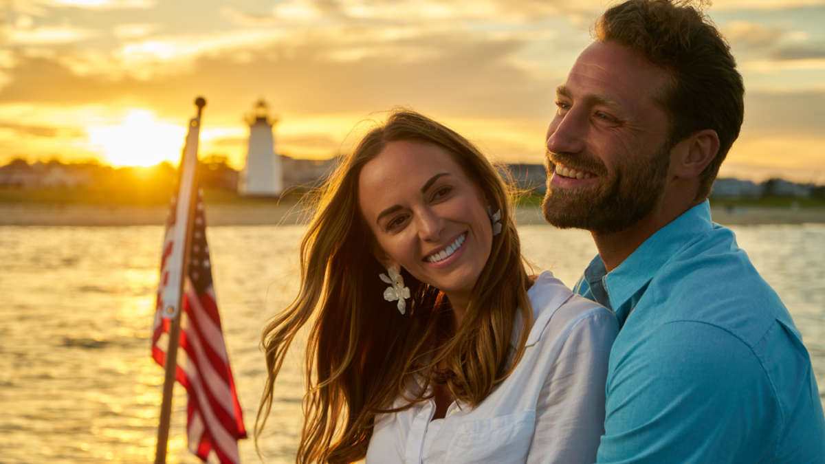 Couple smiling on a boat at sunset