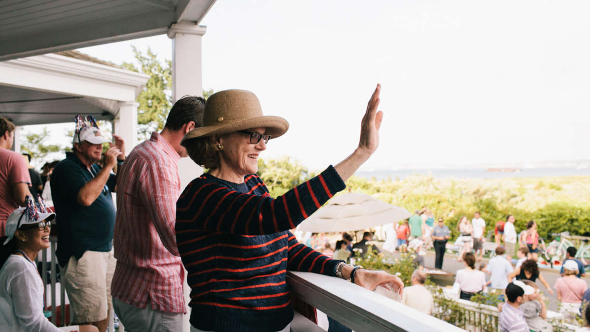 Woman standing on the veranda waving to the parade