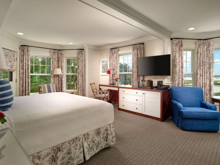 Large bedroom with views from many large windows and a sitting area