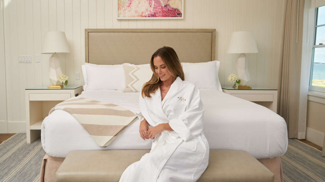 Woman siting on a bench at the foot of the bed