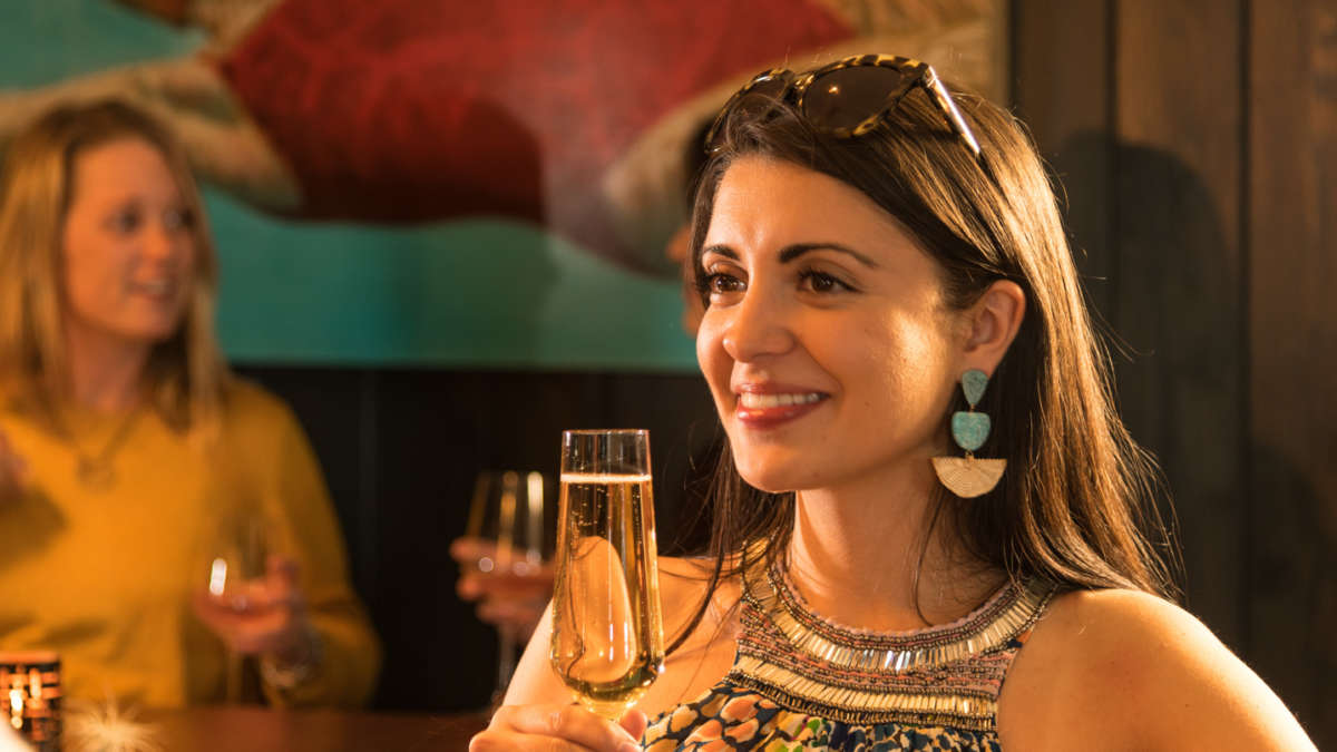 Woman at the bar smiling with a champaign glass