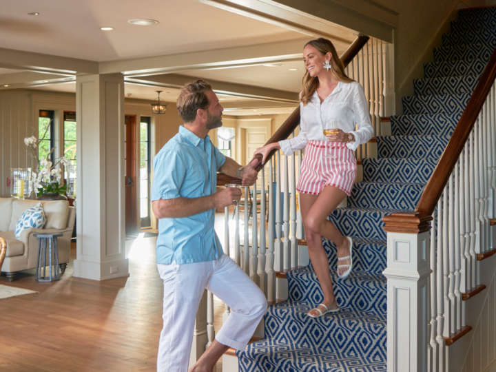 Woman walking down lobby stairs to meet her husband