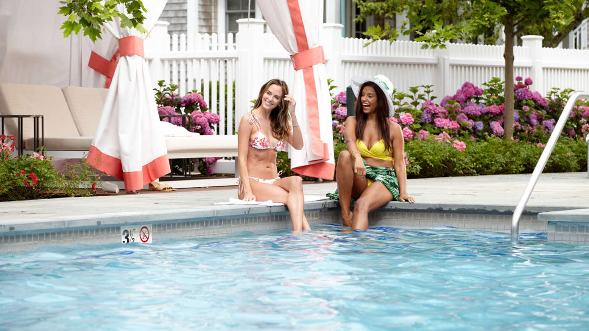 Two women sitting poolside together