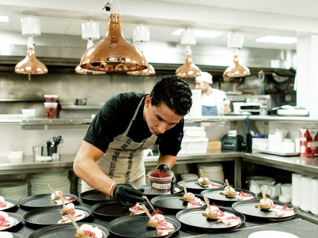 Chef Alex Pineda putting finishing touches on a dish in the kicthen
