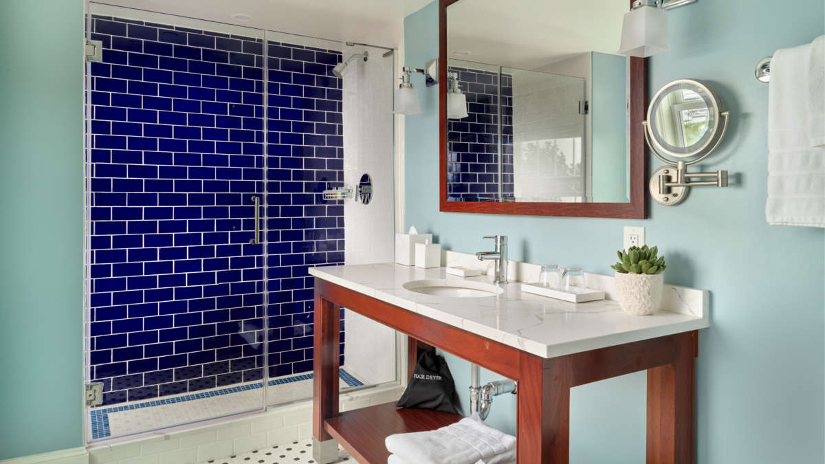 Large bathroom with blue tile in shower