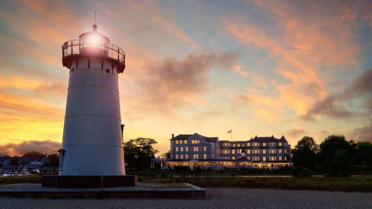 Lighthouse in the foreground and hotel in the background at sunset