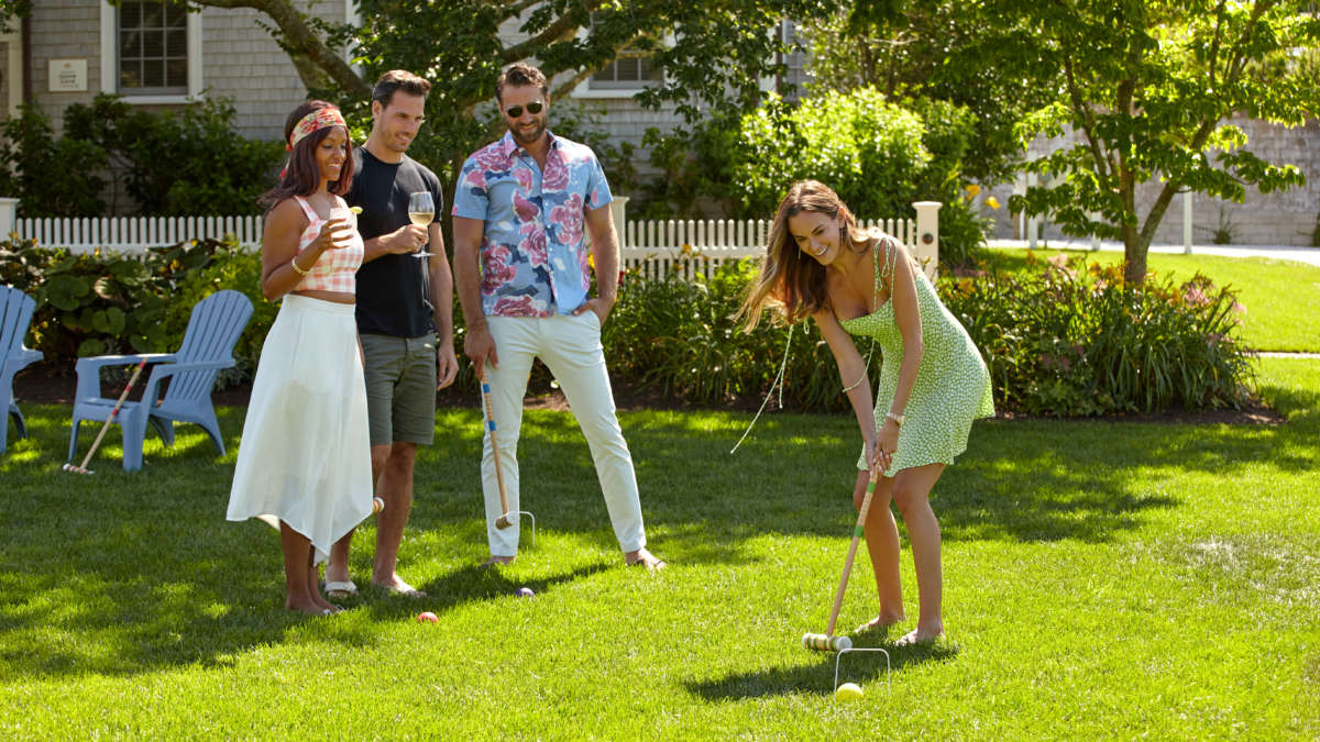 Two couples chatting with drinks playing croquet on the lawn