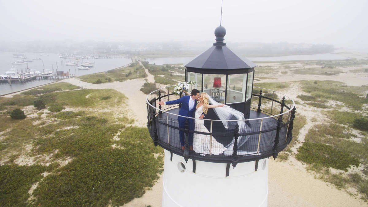 Bride and groom kissing at the top of the lighthouse